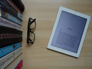 Varios libros impresos, junto a un ebook.